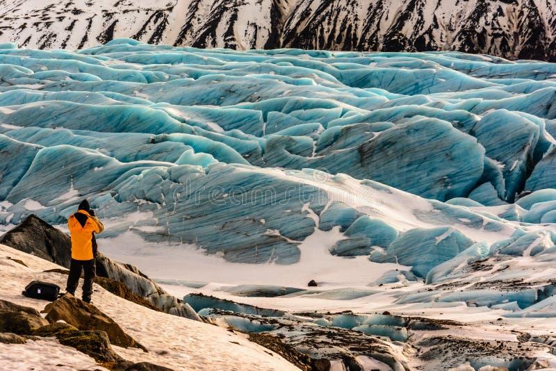 Ταξιδιώτης που εξετάζει τον παγετώνα στην Ισλανδία στοκ φωτογραφίες
