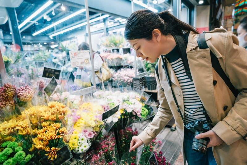 Ταξιδιώτης που επιλέγει τα λουλούδια έξω από το ανθοπωλείο στοκ εικόνες