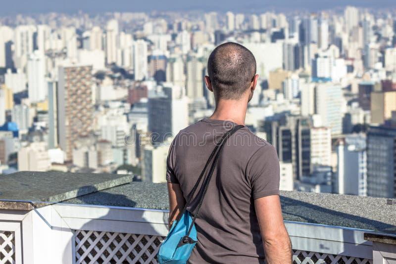 Ταξιδιώτης που κοιτάζει σε μια μεγάλη πόλη, ένα ταξίδι και μια ενεργό έννοια τρόπου ζωής στοκ εικόνα