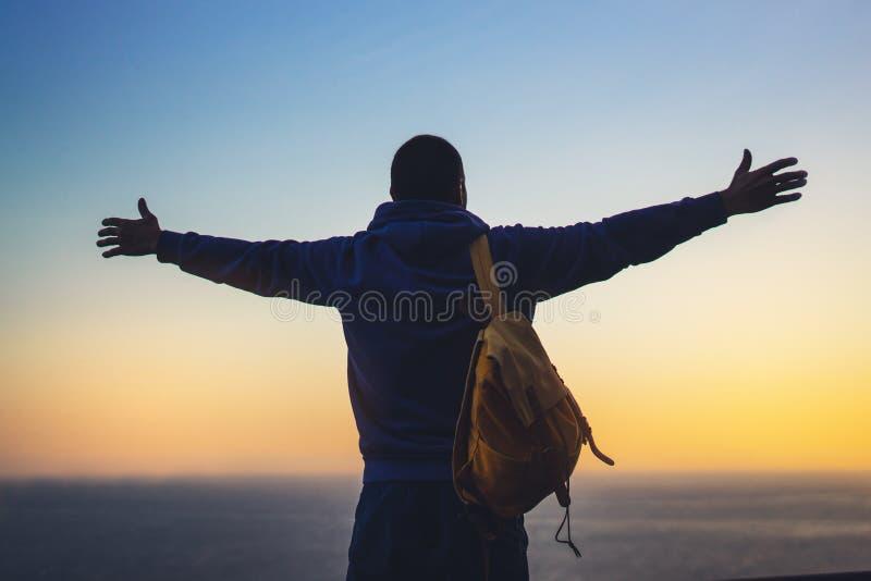 Ταξιδιώτης τουριστών με το σακίδιο πλάτης που στέκεται με τα αυξημένα χέρια, οδοιπόρος που κοιτάζουν στο ηλιοβασίλεμα στην κοιλάδ στοκ φωτογραφία