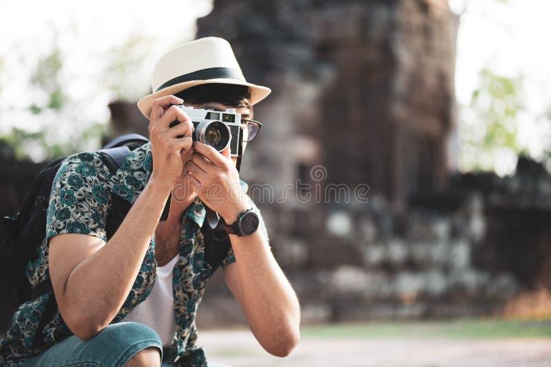 Ταξιδιώτης φωτογράφων νεαρών άνδρων με το σακίδιο πλάτης που παίρνει τη φωτογραφία με τη κάμερα του, Σινικό Τείχος στο υπόβαθρο σ στοκ φωτογραφίες