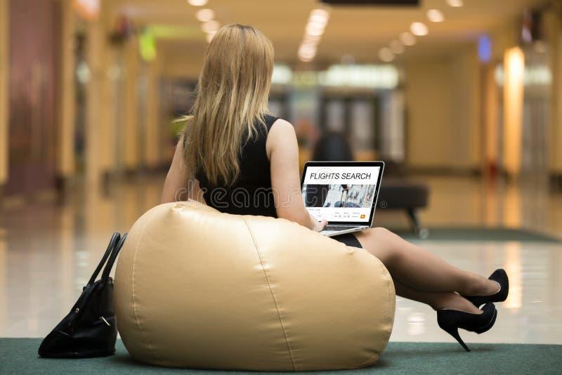 Ταξιδιωτική περιστασιακή γυναίκα που φαίνεται μια πτήση on-line στοκ εικόνες με δικαίωμα ελεύθερης χρήσης