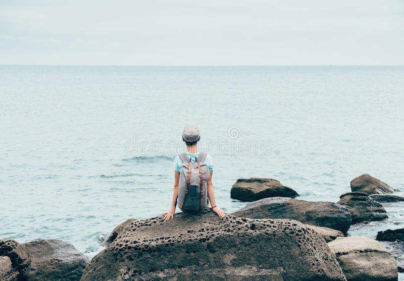 Ταξιδιωτικό κορίτσι που στηρίζεται στην ακτή πετρών στοκ φωτογραφίες με δικαίωμα ελεύθερης χρήσης