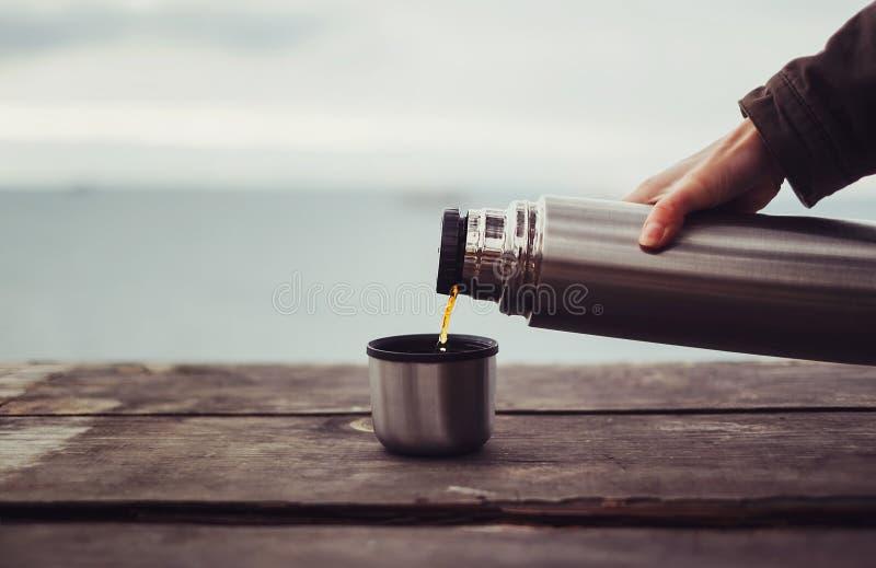 Ταξιδιωτικό χύνοντας τσάι από τα thermos στοκ φωτογραφία