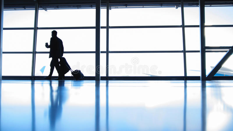 Ταξιδιώτες - διοικητής αεροσκαφών με τον καφέ για να πάει στον αερολιμένα μπροστά από το παράθυρο, σκιαγραφία στοκ εικόνα με δικαίωμα ελεύθερης χρήσης