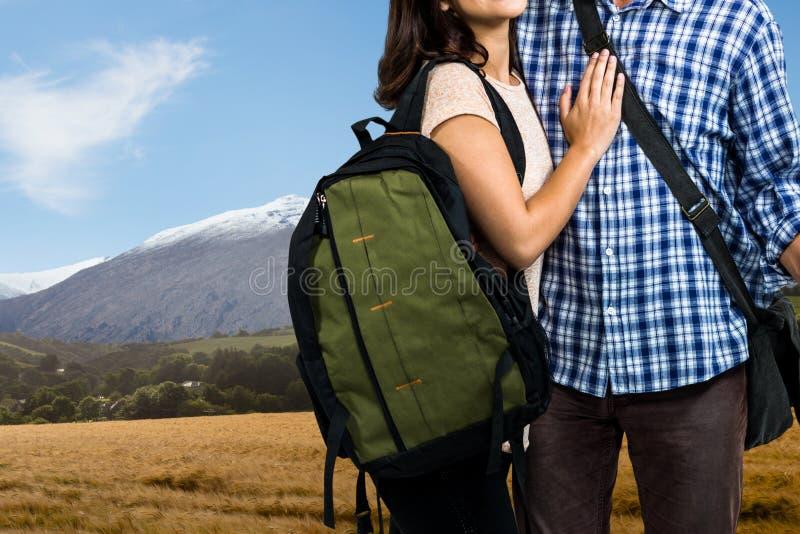 ταξιδιώτες που φέρνουν την τσάντα, βραχίονας στο βραχίονα, στο κλίμα τοπίων βουνών στοκ εικόνες
