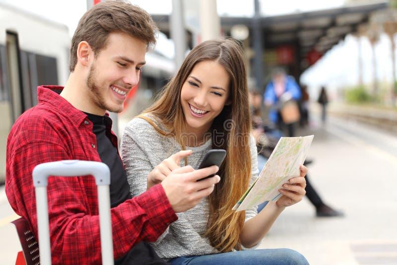 Ταξιδιώτες τουριστών που συμβουλεύονται το ΠΣΤ και τον οδηγό σε έναν σταθμό τρένου στοκ φωτογραφία με δικαίωμα ελεύθερης χρήσης
