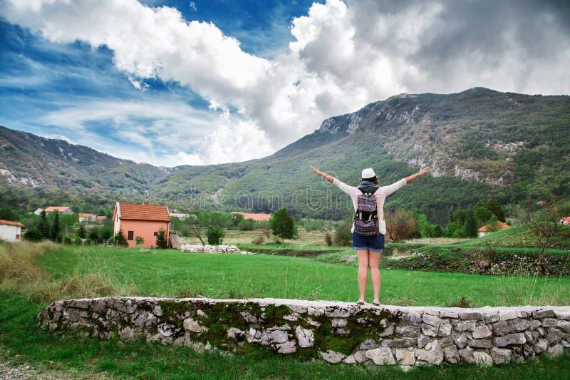 Ταξιδιώτης γυναικών με το σακίδιο πλάτης κοντά στα βουνά στοκ φωτογραφία