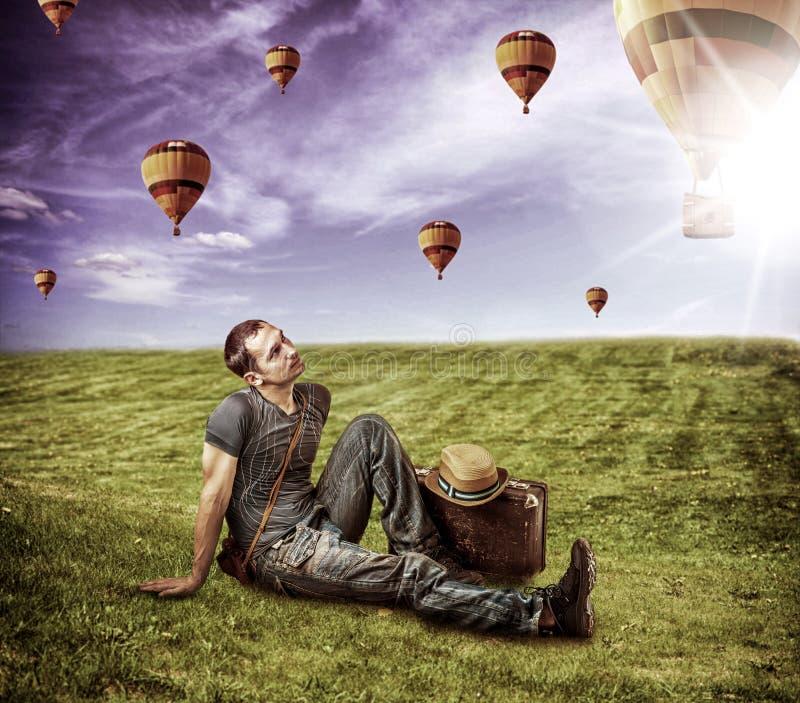 Ταξιδιώτης νεαρών άνδρων και πετώντας αερόστατα στοκ εικόνες με δικαίωμα ελεύθερης χρήσης
