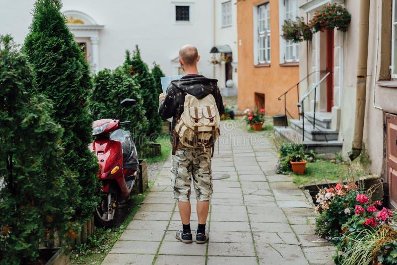 Ταξιδιώτης νεαρών άνδρων που φαίνεται χάρτης πόλεων στην παλαιά κωμόπολη στοκ φωτογραφία με δικαίωμα ελεύθερης χρήσης