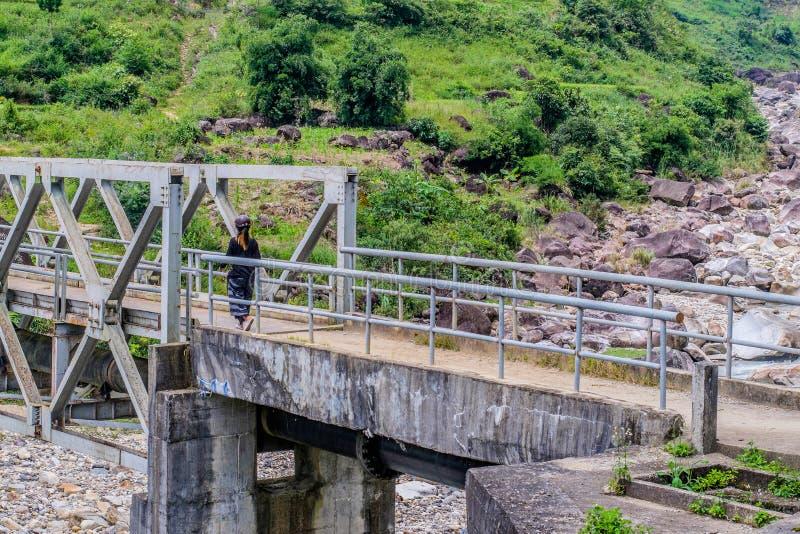 Ταξιδιώτης που περπατά στην άσπρη γέφυρα χάλυβα επάνω από το δασικό ρεύμα στοκ φωτογραφία