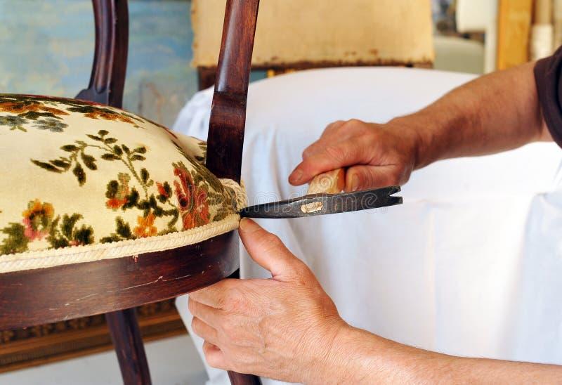 Ταπετσιέρης που ευθυγραμμίζει το κάθισμα μιας καρέκλας στοκ εικόνες