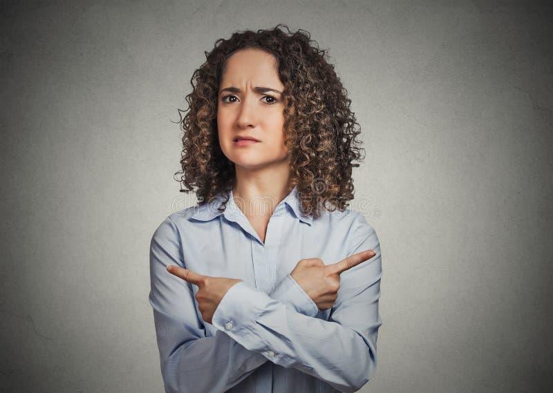 Ταραγμένη νέα γυναίκα που δείχνει σε δύο διαφορετικές κατευθύνσεις στοκ φωτογραφία με δικαίωμα ελεύθερης χρήσης