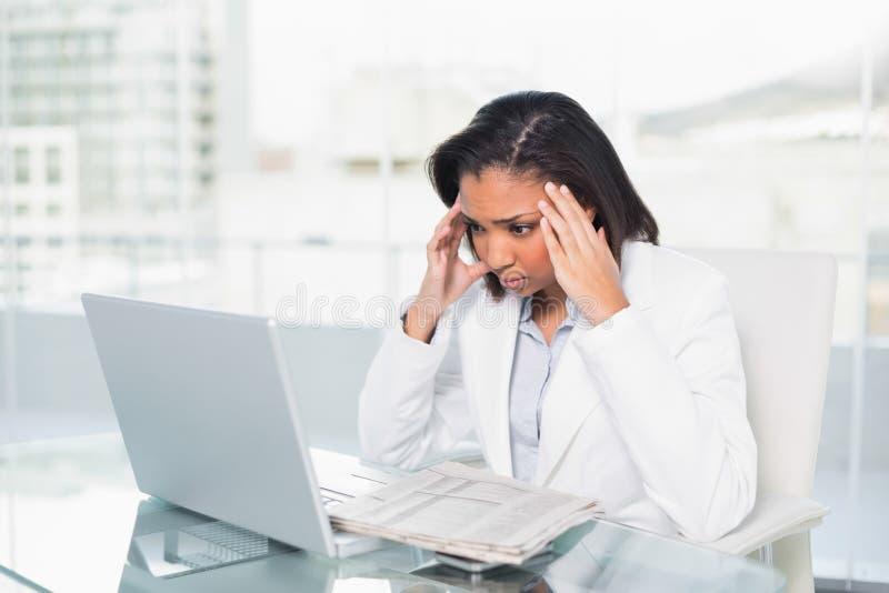 Ταραγμένη νέα μελαχροινή μαλλιαρή επιχειρηματίας που προσπαθεί να καταλάβει ένα έγγραφο στοκ εικόνες