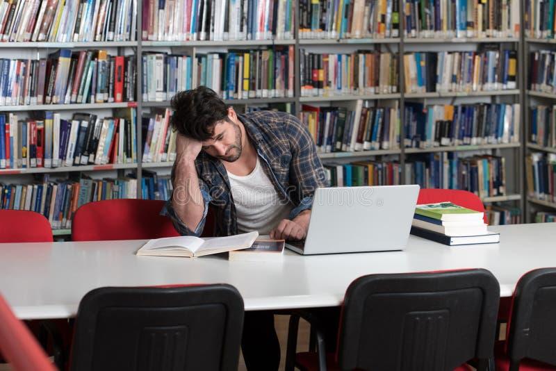 Ταραγμένος άνδρας σπουδαστής που διαβάζει πολλά βιβλία για το διαγωνισμό στοκ εικόνα