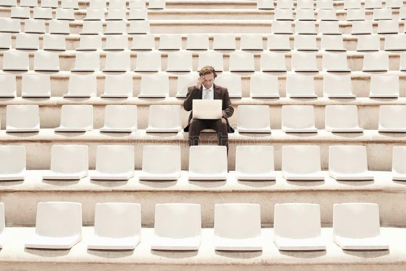 Ταραγμένος επιχειρηματίας που εργάζεται στο lap-top στο κέντρο κενού Audito στοκ φωτογραφία με δικαίωμα ελεύθερης χρήσης