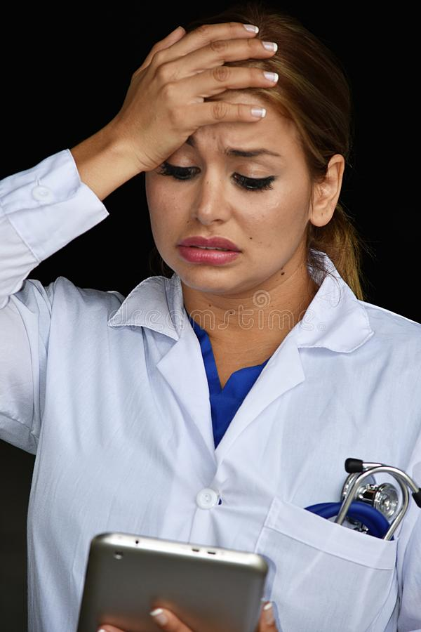 Ταραγμένος θηλυκός γιατρός γιατρών που φορά το παλτό εργαστηρίων με την ταμπλέτα στοκ φωτογραφία