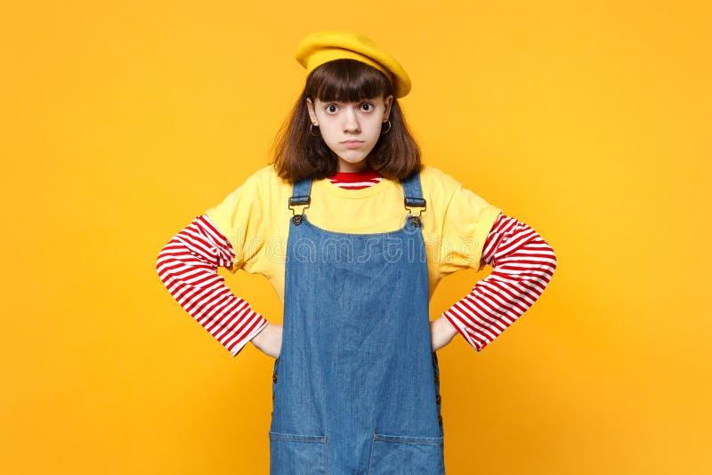 Ταραγμένος μπερδεμένος έφηβος κοριτσιών γαλλικό beret, τζιν sundress που στέκεται με τα όπλα σε μεσολαβή που απομονώνει στον κίτρ στοκ εικόνες με δικαίωμα ελεύθερης χρήσης
