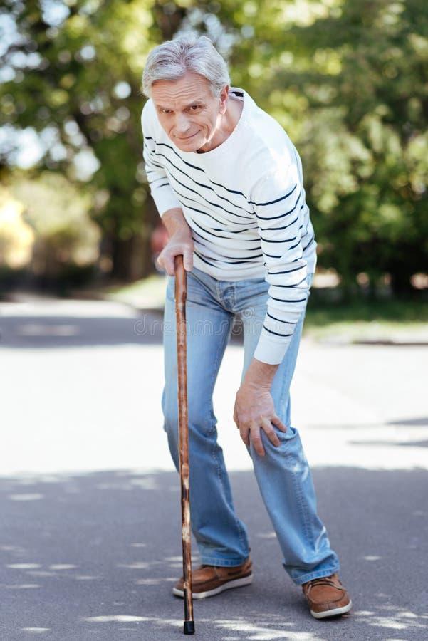 Ταραγμένος συνταξιούχος που αισθάνεται τον πόνο στο γόνατο υπαίθρια στοκ εικόνες
