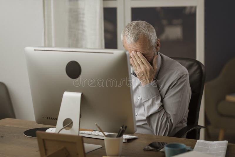 Ταραγμένο άτομο τρίτης ηλικίας που χρησιμοποιεί έναν υπολογιστή στοκ φωτογραφίες με δικαίωμα ελεύθερης χρήσης