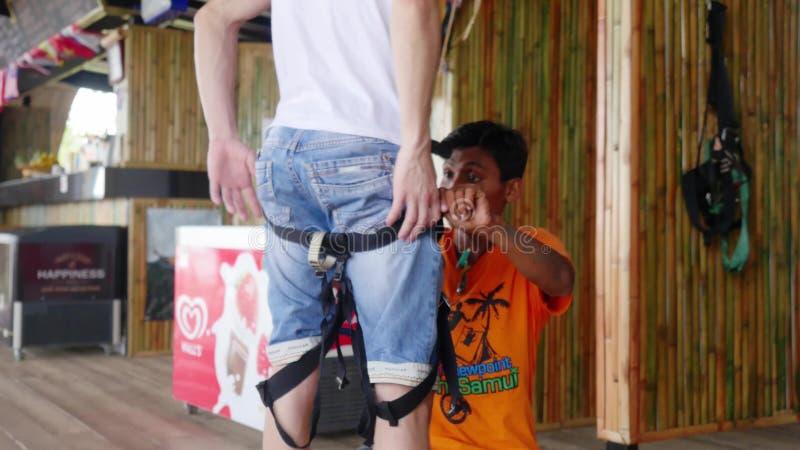 Ταϊλάνδη, Koh Samui, στις 26 Ιανουαρίου 2016 Canyoning ο εκπαιδευτικός φορά τον εξοπλισμό για την κάθοδο μέσω των βουνών από στοκ φωτογραφία