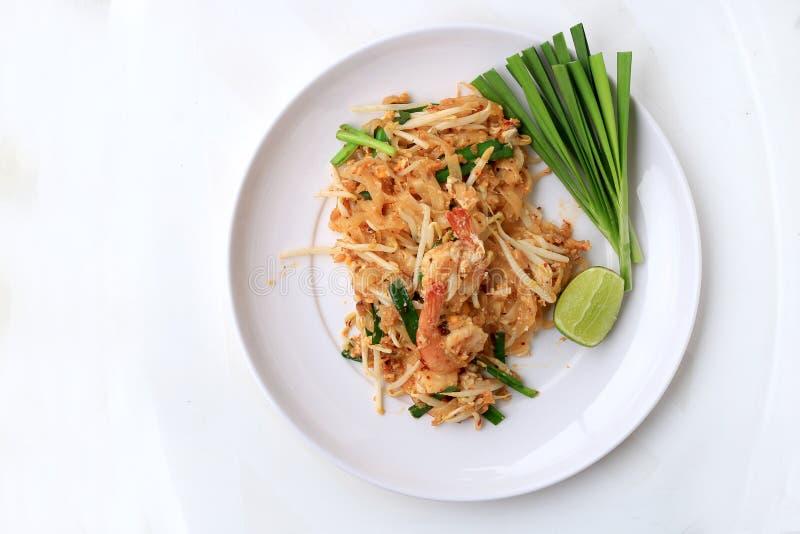 Ταϊλανδικά, ανακατώνω-τηγανισμένα νουντλς ρυζιού μαξιλαριών με τις γαρίδες στο άσπρο πιάτο με το λεμόνι φωτογραφικών διαφανειών κ στοκ εικόνες