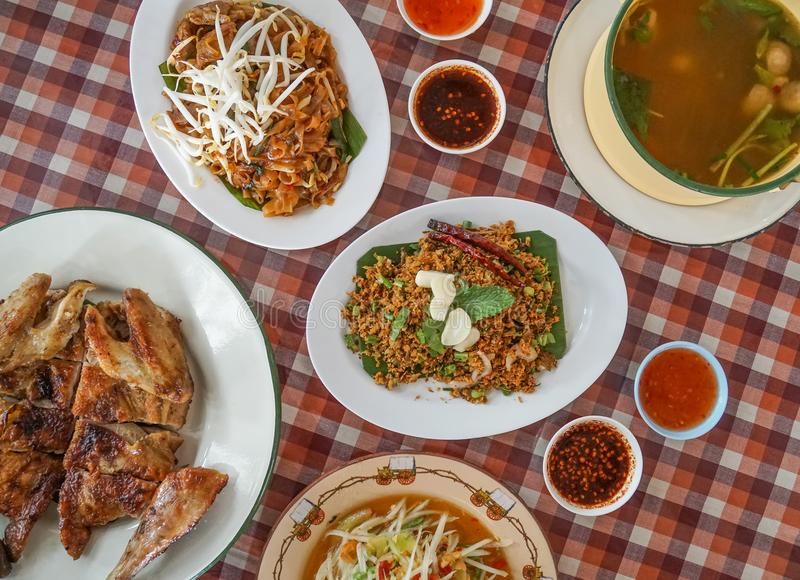 Ταϊλανδικά βορειοανατολικά παραδοσιακά τρόφιμα, ψημένο στη σχάρα κοτόπουλο, ανακατώνω-τηγανισμένο νουντλς, papaya σαλάτα, ξινή πι στοκ εικόνες