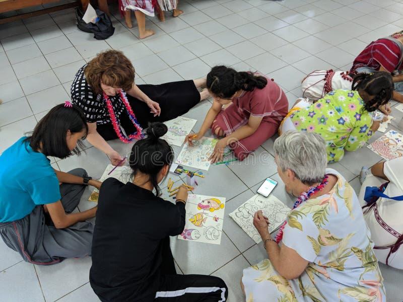 Ταϊλανδικά παιδιά που χρωματίζουν με τους καυκάσιους ενηλίκους στοκ φωτογραφία