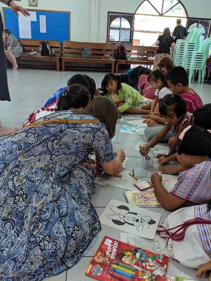 Ταϊλανδικά παιδιά που χρωματίζουν με τους καυκάσιους ενηλίκους στοκ φωτογραφίες με δικαίωμα ελεύθερης χρήσης