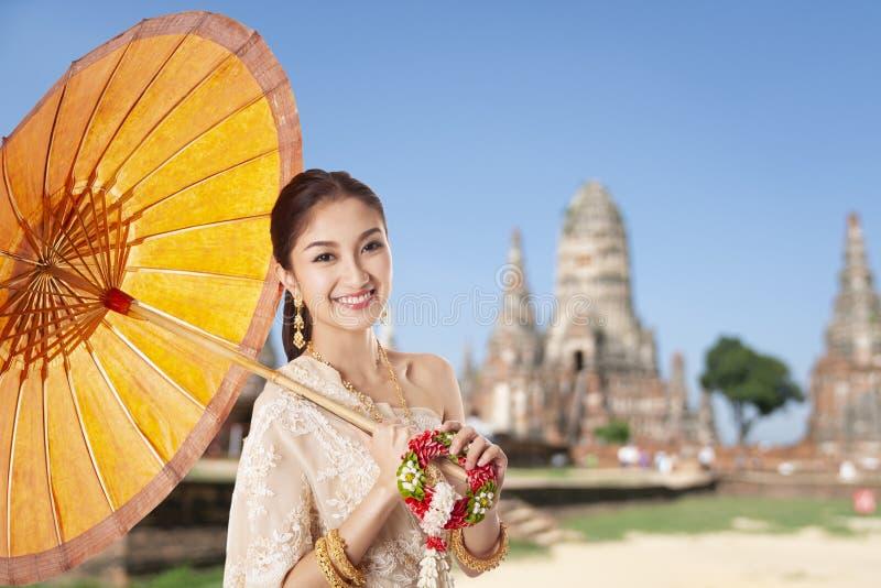 Ταϊλανδική ασιατική υποδοχή γυναικών με το παραδοσιακές ταϊλανδικές κοστούμι και την ομπρέλα στο υπόβαθρο ναών στοκ φωτογραφία