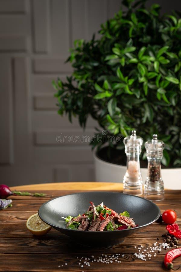 Ταϊλανδική σαλάτα βόειου κρέατος στο μαύρο πιάτο στο ξύλινο υπόβαθρο στοκ εικόνα με δικαίωμα ελεύθερης χρήσης