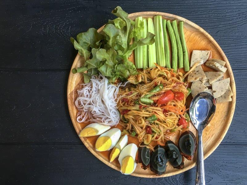Ταϊλανδικός papaya δίσκος σαλάτας στον ξύλινο πίνακα, ταϊλανδικά πικάντικα τρόφιμα και φρέσκα συστατικά χορταριών στα ξύλινα τοπ  στοκ φωτογραφία