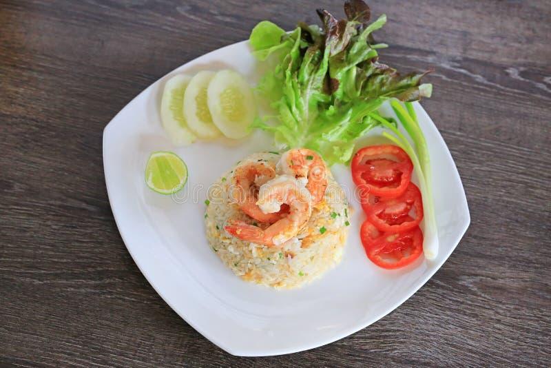 Ταϊλανδικό τηγανισμένο ύφος ρύζι με τις γαρίδες στο άσπρο πιάτο ενάντια στον ξύλινο πίνακα Διακόσμηση τροφίμων με τα λαχανικά στοκ φωτογραφίες