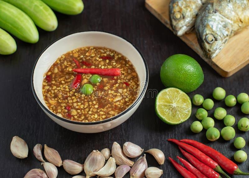 Ταϊλανδικό kapi γλωσσικού Nam κολλών τσίλι prik σε ένα άσπρο κύπελλο με τα συστατικά και τηγανισμένο σκουμπρί ατμού στον πίνακα στοκ εικόνες