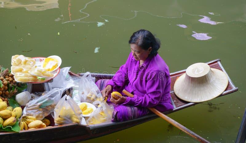 Ταϊλανδικές γυναίκες που πωλούν τα φρούτα να επιπλεύσει στην αγορά στοκ εικόνες