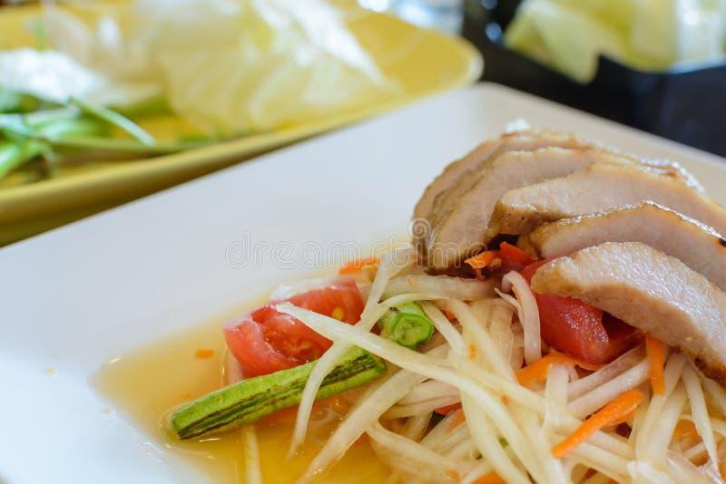Ταϊλανδική papaya σαλάτα στο άσπρο πιάτο με το ψημένο στη σχάρα χοιρινό κρέας στοκ εικόνα με δικαίωμα ελεύθερης χρήσης