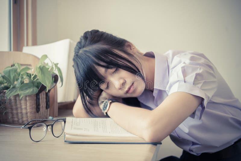Ταϊλανδικό κορίτσι γυμνασίου το ομοιόμορφο φθινόπωρο κοιμισμένο στο βιβλίο στο γραφείο της κατά τη διάρκεια να κάνει την εργασία στοκ φωτογραφία