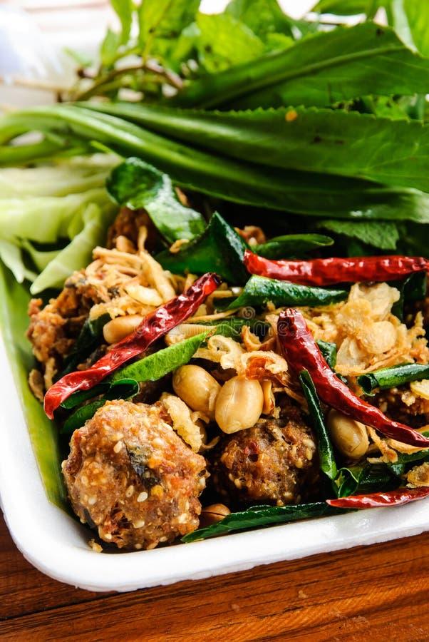 Ταϊλανδικό πιάτο: Τηγανισμένο πικάντικο κομματιασμένο χοιρινό κρέας με το χορτάρι στοκ εικόνα