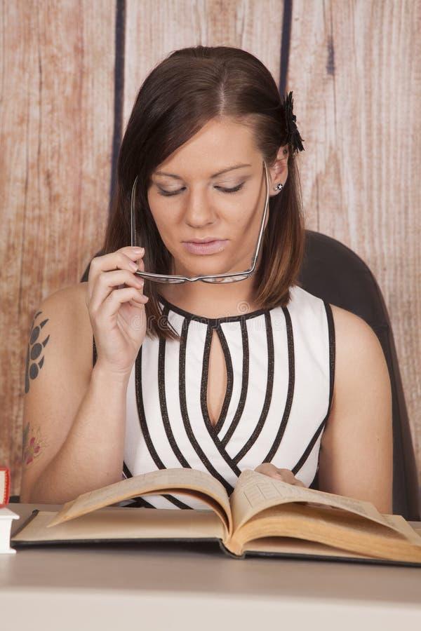 Τα άσπρα γυαλιά βιβλίων γραφείων φορεμάτων γυναικών κοιτάζουν κάτω στοκ φωτογραφία με δικαίωμα ελεύθερης χρήσης