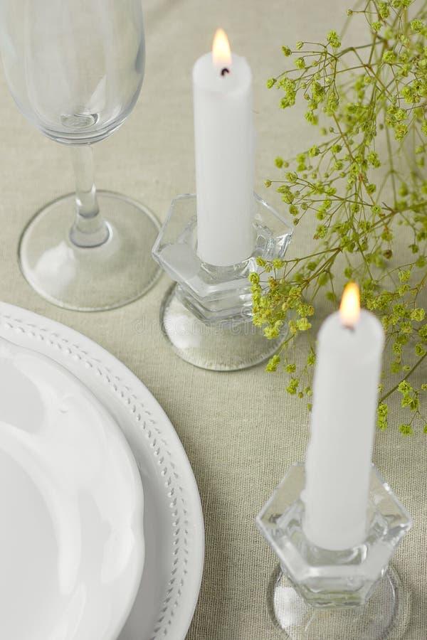 Τα άσπρα εκλεκτής ποιότητας κενά LIT γυαλιού κρασιού πιάτων κολλούν τα κίτρινα λουλούδια ανοίξεων κεριών στο μπεζ επιτραπέζιο ύφα στοκ εικόνα με δικαίωμα ελεύθερης χρήσης