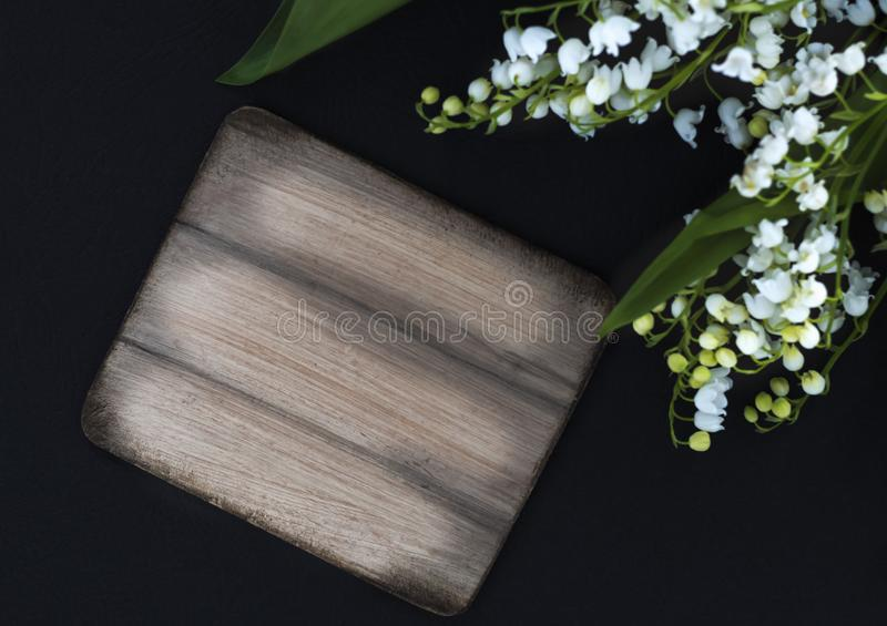 Τα άσπρα λουλούδια μπορούν κρίνοι της κοιλάδας σε ένα μαύρο υπόβαθρο με ένα αντίγραφο του διαστήματος στοκ φωτογραφίες