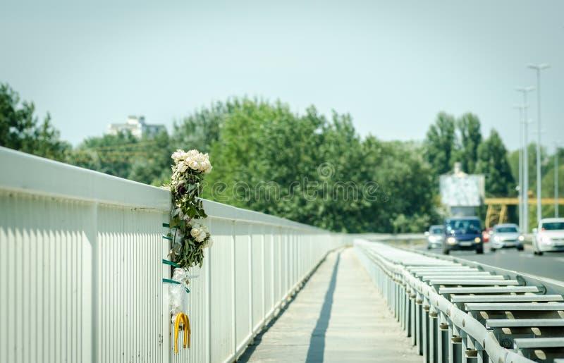 Τα άσπρα λουλούδια τριαντάφυλλων στην περιοχή ενός τροχαίου ατυχήματος τροχαίου ατυχήματος στο μέταλλο ασφάλειας γεφυρών περιφράζ στοκ εικόνες