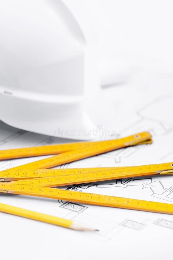 Τα άσπρα σκληρά εργαλεία πλησίον εργασίας καπέλων, κλείνουν επάνω στοκ εικόνες με δικαίωμα ελεύθερης χρήσης