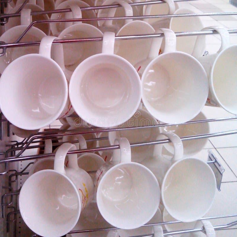 Τα άσπρα φλυτζάνια κρεμούν σε μια σειρά στοκ εικόνα με δικαίωμα ελεύθερης χρήσης