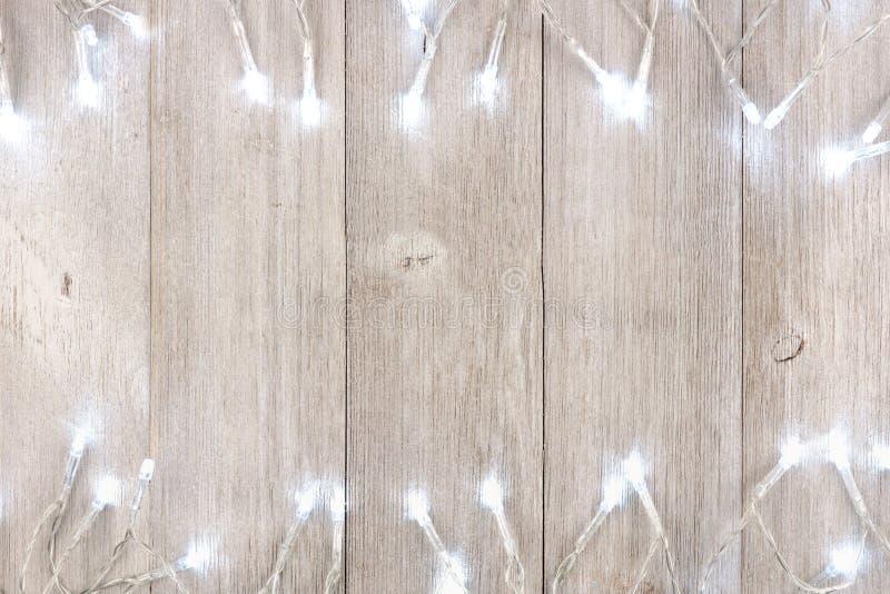 Τα άσπρα Χριστούγεννα ανάβουν τα διπλά σύνορα πέρα από το ανοικτό γκρι ξύλο στοκ εικόνες