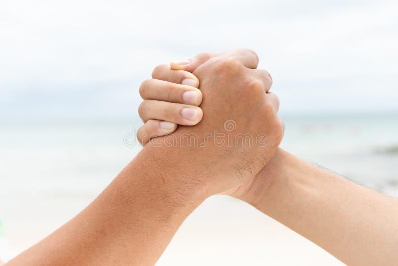 Τα άτομα δίνουν το κούνημα που διατηρεί τη συνοχή στο θολωμένο υπόβαθρο θάλασσας και ουρανού στοκ φωτογραφία με δικαίωμα ελεύθερης χρήσης