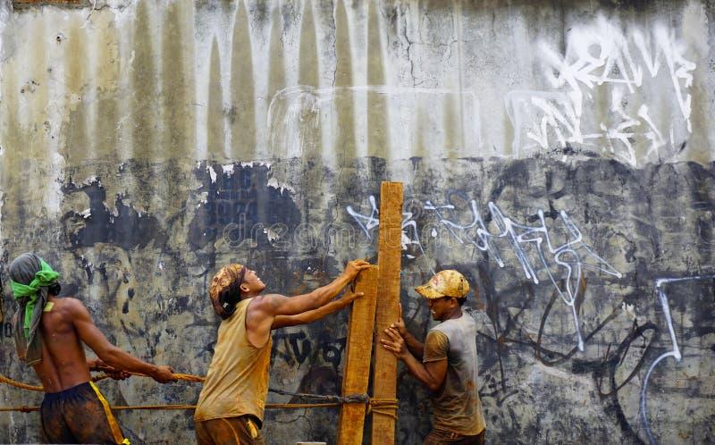 Τα άτομα εργάζονται σκληρά μαζί για να δημιουργήσουν τα ξύλινα κούτσουρα στοκ φωτογραφία