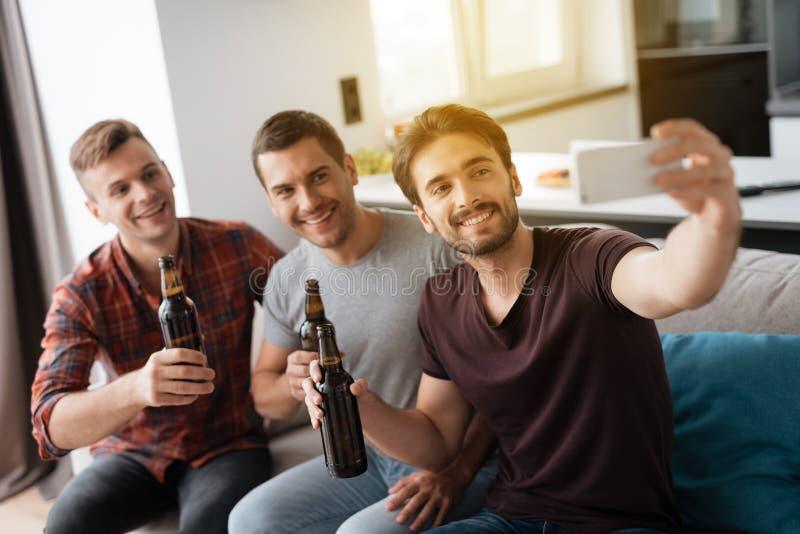 Τα άτομα κάθονται στον καναπέ και την μπύρα κατανάλωσης Ένα άτομο κάνει ένα selfie με τους φίλους και την μπύρα στοκ φωτογραφίες με δικαίωμα ελεύθερης χρήσης