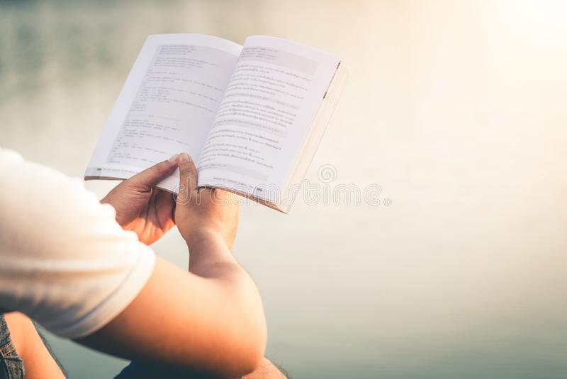 Τα άτομα κάθονται το βιβλίο ανάγνωσης στην ήρεμη φύση στοκ εικόνα