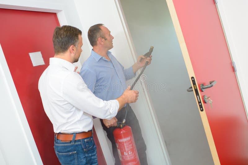 Τα άτομα με τον πυροσβεστήρα στην πόρτα καπνίζουν το γεμισμένο δωμάτιο στοκ φωτογραφίες με δικαίωμα ελεύθερης χρήσης